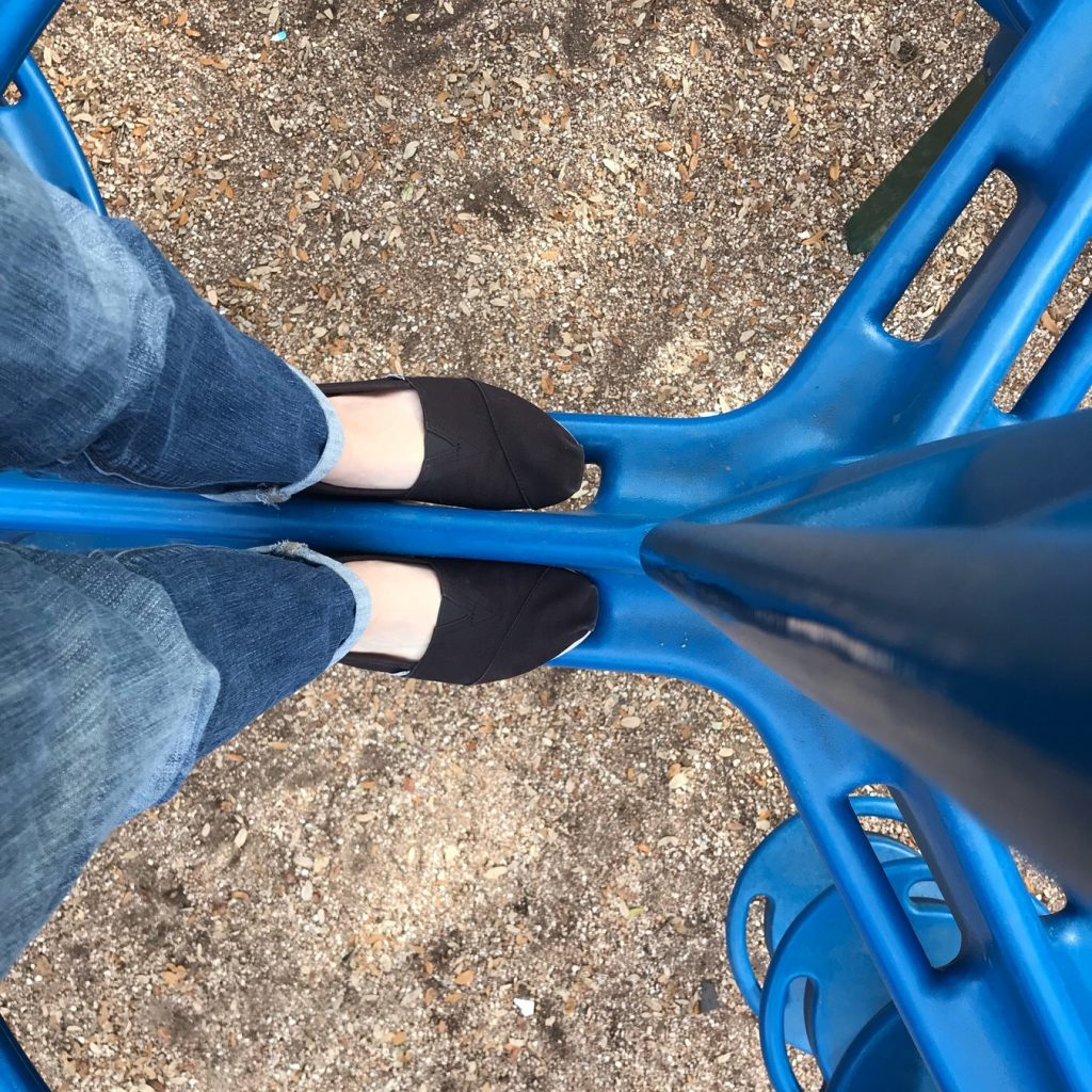 a person's feet standing on top of playground, looking down