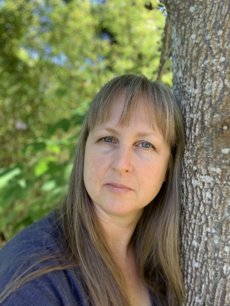 Jill's headshot. She is leaning against a tree outside.