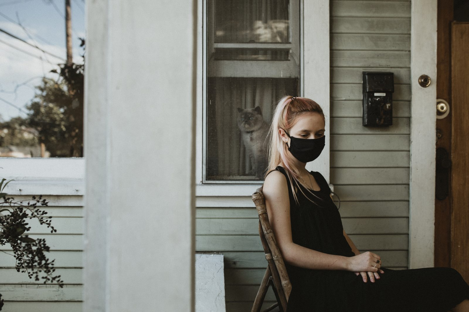 Girl wearing a mask sitting on her porch during the coronavirus lockdown.